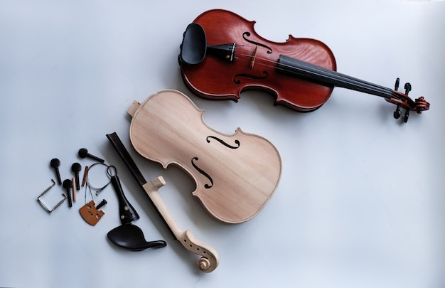 Raw violin with accessory put beside completed violin