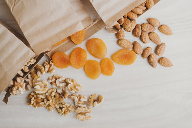 Raw walnut, almond and dried apricot in paper bags on wooden table