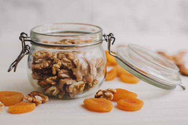 Raw walnut in a glass jar and dried apricot. kitchen food storage