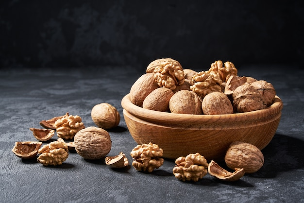 Raw walnut in wooden bowl, close-up.