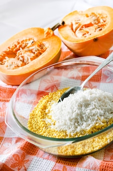 건포도와 우유 호박 죽 요리 과정에서 유리 냄비에 원시 씻어 기장과 쌀