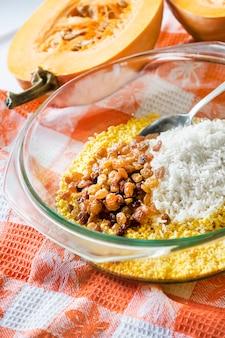 우유 호박 죽 요리 과정에서 유리 냄비에 원시 씻은 기장, 쌀, 건포도