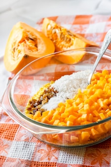 우유 호박 죽 요리 과정에서 유리 냄비에 원시 씻어 기장, 쌀, 건포도 및 호박