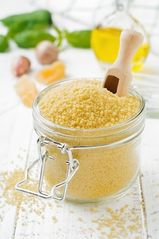 Raw wheat cereals couscous in a glass jar on a light concrete or stone background traditional food of north africa and southern europe