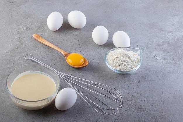 石のテーブルに置かれた小麦粉とミルクと生の白い鶏の卵。