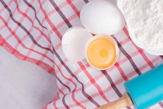 흰 탁자에 밀가루를 얹은 생 계란.