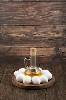 Сырые белые яйца и бутылка оливкового масла на деревянной доске.