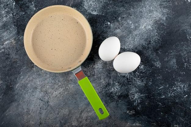 空の鍋の横にある生の白い卵。