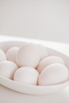 テーブルの上のプレート上の生の白い卵。