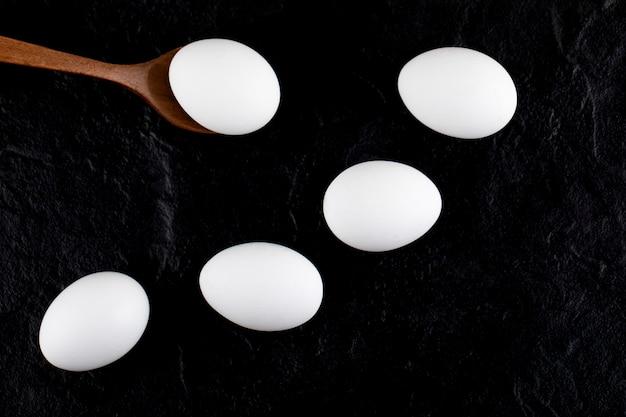 Uova bianche crude e cucchiaio di legno sulla superficie nera.