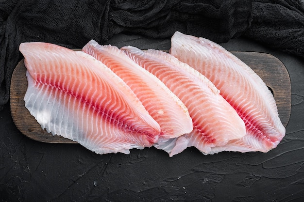 Филе сырой белой рыбы, на черном столе, вид сверху