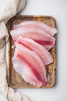 Филе сырой белой рыбы, на белом столе, вид сверху