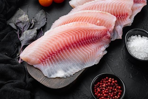 黒いテーブルの上にバスマティライスとチェリートマトの材料を使った生の白身魚のティラピア