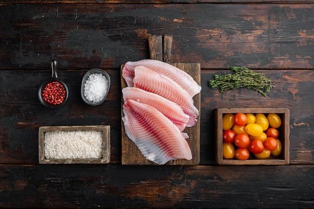 Сырая белая рыба тилапия, с рисом басмати и ингредиентами из помидоров черри, на темном деревянном столе, вид сверху