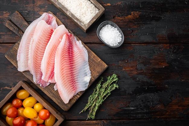 生の白身魚のティラピア、バスマティライスとチェリートマトの材料、暗い木製のテーブル、上面図