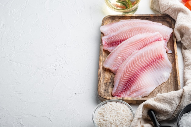 生の白身魚のティラピア、バスマティライスとチェリートマトの材料、白いテーブル、上面図