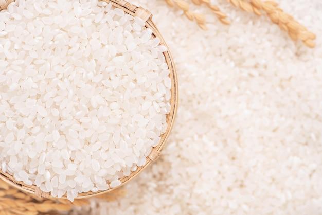 茶色のボウル、有機農業のデザインコンセプトの白い背景に生の白い磨かれた製粉食用米作物。アジアの主食、クローズアップ。