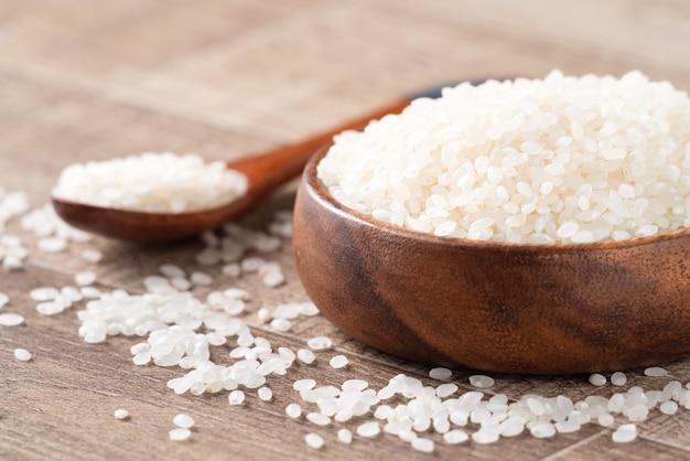 유기농 디자인 컨셉의 나무 탁자 배경에 있는 순백색의 맷돌로 된 식용 쌀.