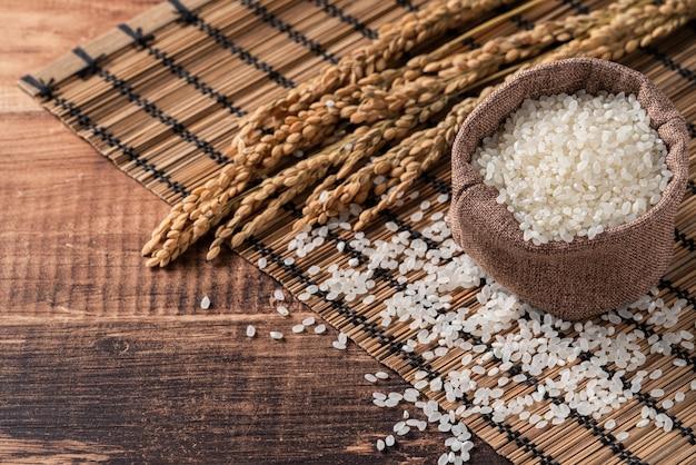 ボウルの木製テーブルの背景に生の白い磨かれた粉砕食用米、有機的なデザインコンセプト。