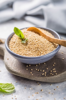 Raw  white quinoa seeds (lat. chenopodium quinoa) on  plate with wooden spoon