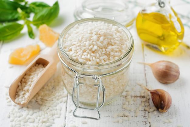 Сырой белый рис сорта арборио для итальянских блюд ризотто в стеклянной банке на белом бетонном или каменном фоне.
