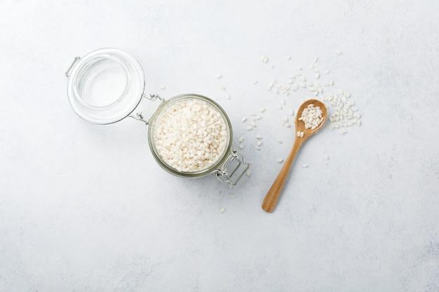 Сырой белый рис сорта арборио для итальянских блюд ризотто в стеклянной банке на белом бетоне или камне.