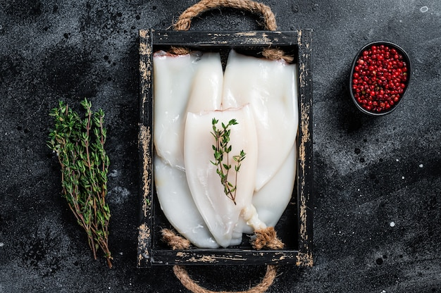 Raw white squid or calamari in a wooden tray with herbs. black background. top view.