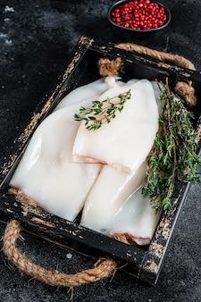 허브와 함께 나무 쟁반에 원시 흰 오징어 또는 오징어