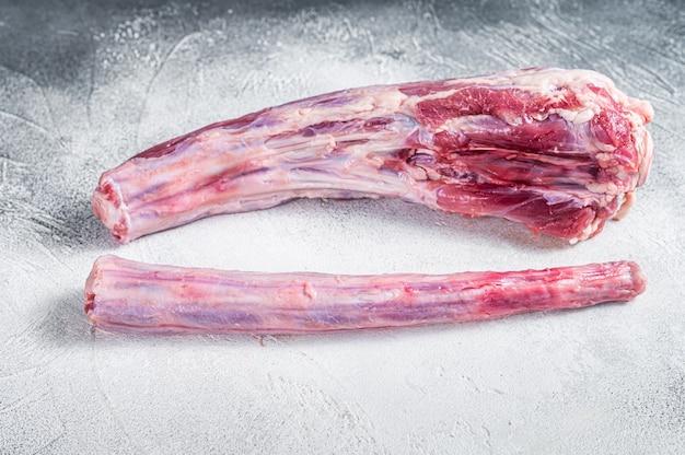 정육점 테이블에 원시 전체 쇠고기 송아지 고기 oxtail 고기입니다. 흰 바탕. 평면도.