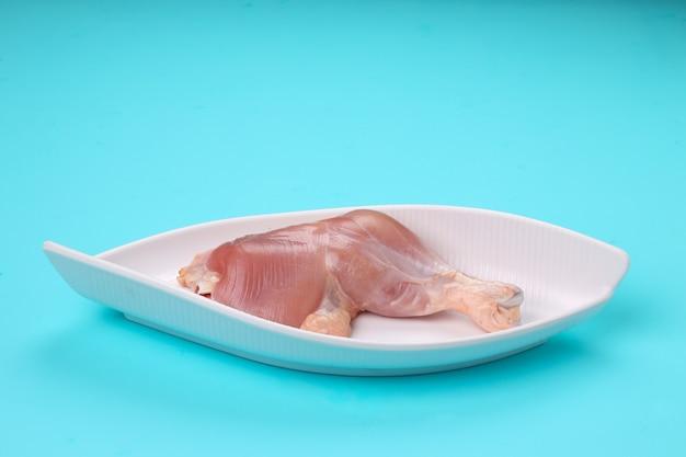 껍질이 없는 생 닭다리를 아름다운 타원형 모양의 흰색 식기에 배열