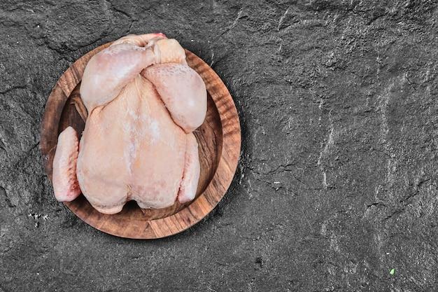 白い表面に分離されたセラミックプレート上の生の丸ごとの鶏肉
