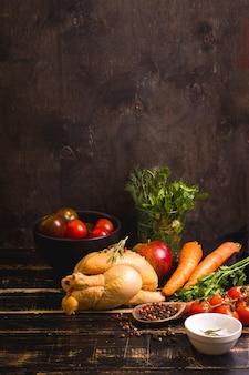Сырая целая курица готова к приготовлению. курица, овощи, зелень, специи на деревенском деревянном фоне