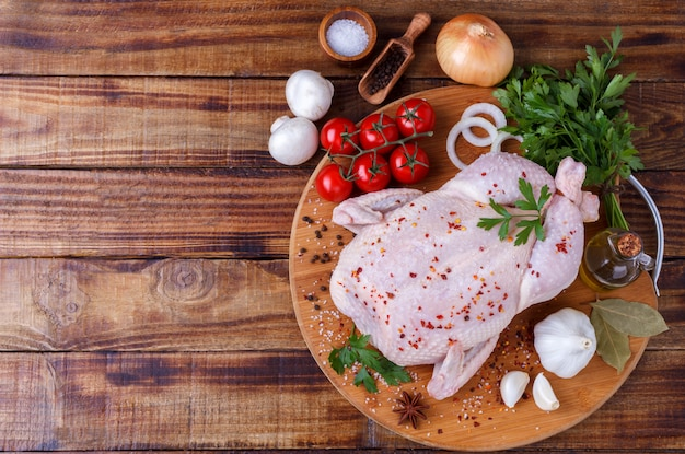 Raw whole chicken with herbs and spices wooden background, top view flat lay copy space