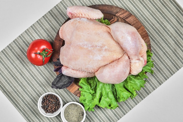 Raw whole chicken on wooden plate with lettuce, tomato and spices