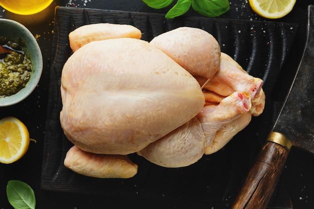 Сырой цельный кукурузный цыпленок со специями на темном столе