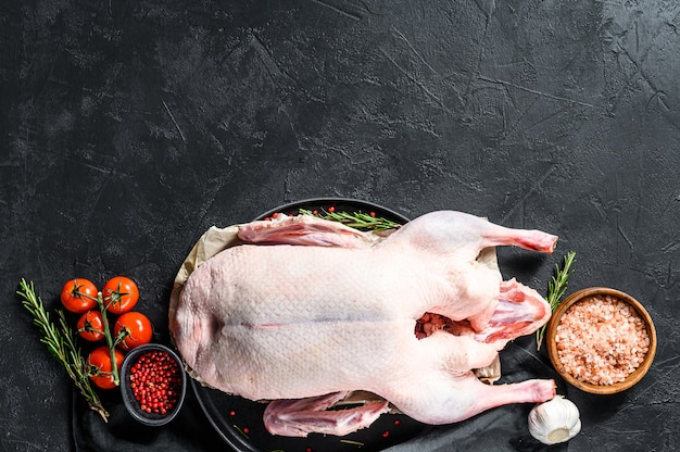 Raw whole duck, pink pepper and rosemary.