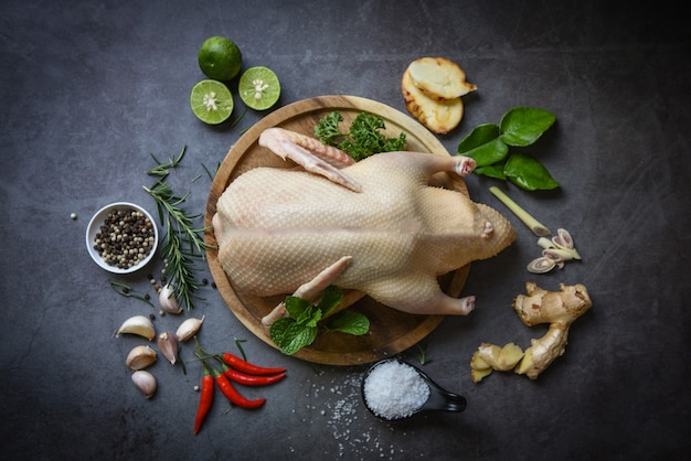 Raw whole duck with herb spices to cook on dark palte, fresh duck meat on wooden tray for food