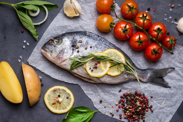 Raw whole fish with fresh ingredients ready to cook. sea bream, lemon, herbs, potato, tomatoes, garlic, spices.