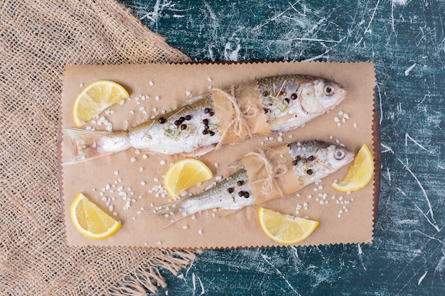 Raw whole fishes with lemon slices, pepper grains and salt on wooden board.