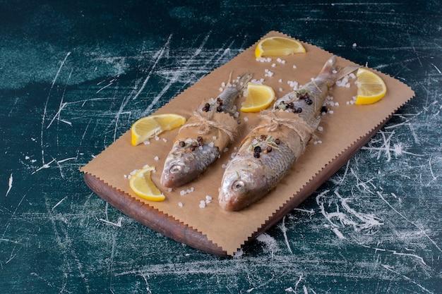 Pesci interi crudi con fette di limone, grani di pepe e sale su tavola di legno.