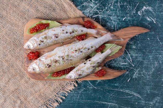 Сырые целые рыбы с красной икрой на деревянной доске.
