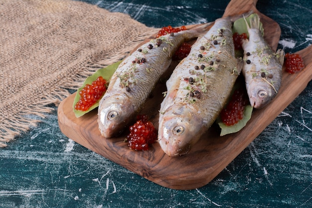 Raw whole fishes with red caviar on wooden board.
