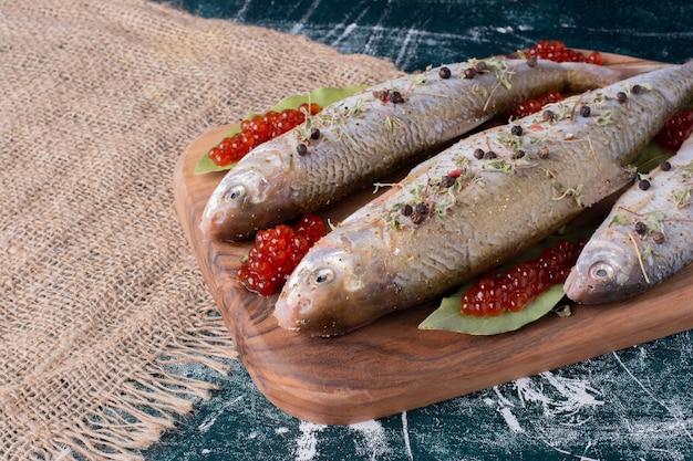 Pesci interi crudi con caviale rosso su tavola di legno.