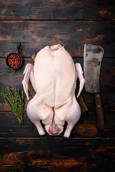 원시 거위, 허브와 함께 설정된 가금류 고기, 오래된 어두운 나무 테이블 배경, 평면도