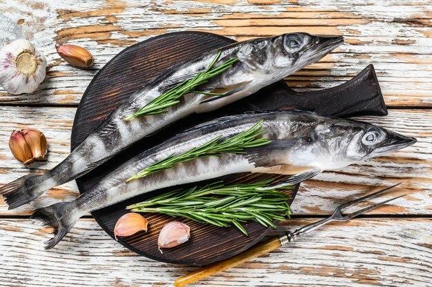 Сырая целая ледяная рыба с травами. белый деревянный фон. вид сверху.