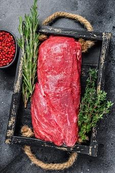 Сырое мясо говядины целиком на деревянном подносе с травами. черный фон. вид сверху.