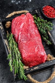 Сырое мясо телятины целиком на деревянном подносе с травами.