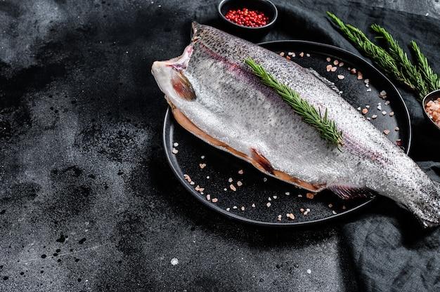 頭がなく、塩とローズマリーが入ったマス全体の生の魚。黒の背景
