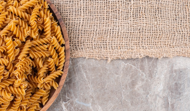 Raw whole wheat fusilli on a wooden plate on a burlap on the marble surface