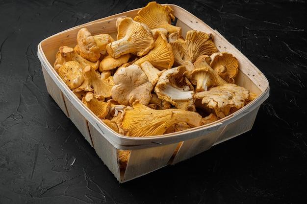 원시 야생 살구 버섯 세트, 나무 상자 컨테이너, 검은색 돌 탁자 배경